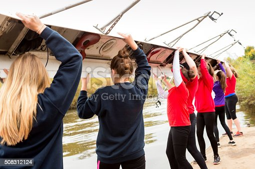 istock Female rowing team put their boat in the water 508312124