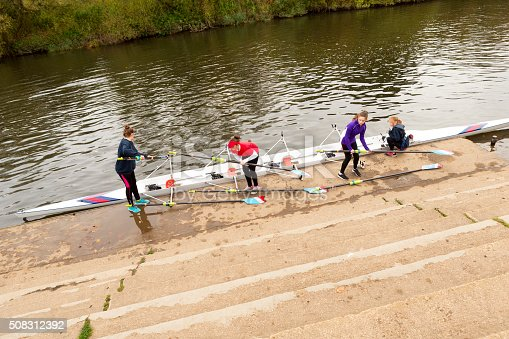 istock Female rowing team putting their boat in the water 508312392