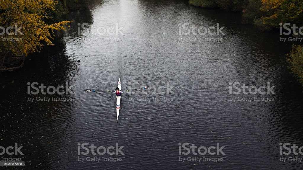 Female Rowing Up River stock photo