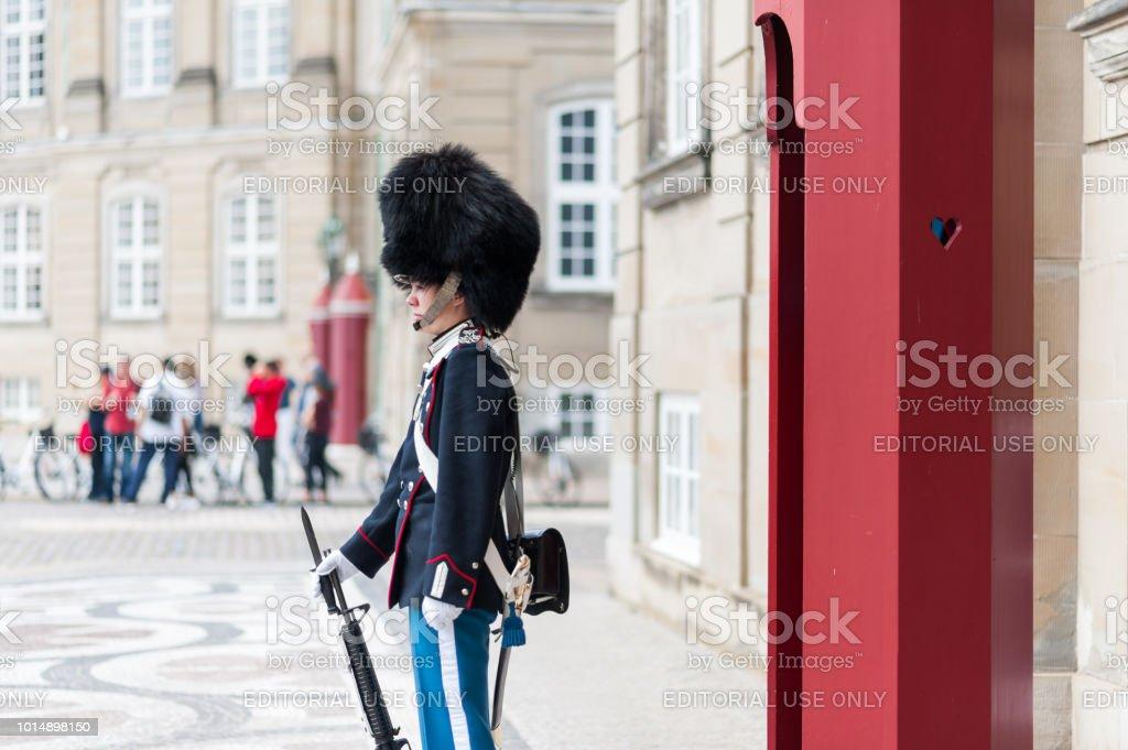 Female royal guard (Royal Life Guard) standing in front of the Levetzau's Palace, Amalienborg Square. stock photo