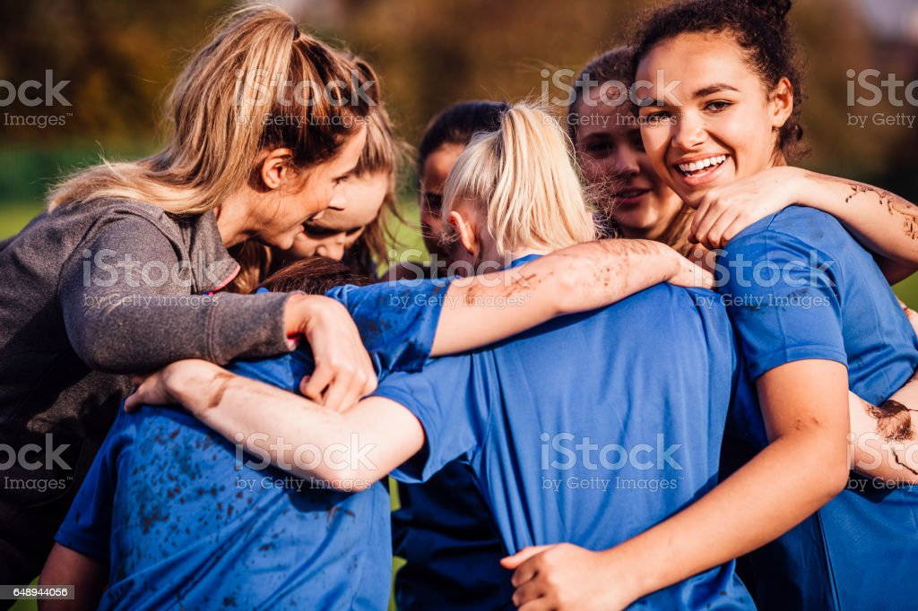 Female Rugby Players Together in a Huddle stock photo