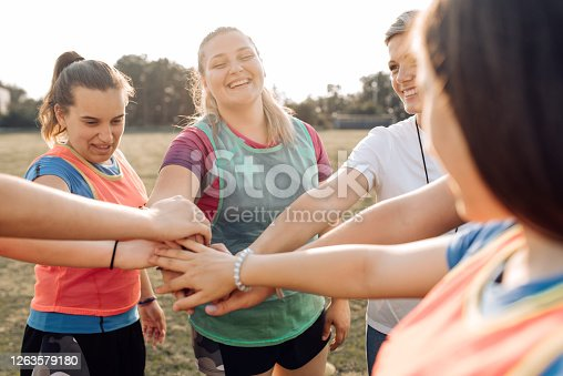 Female rugby team and their coach gathering and cheering for their success.