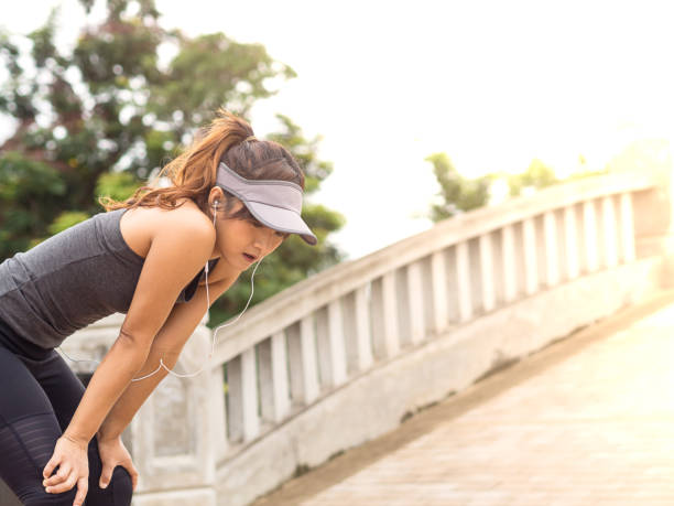 Female runner athlete resting and catching the breath after marathon training in the park at sunset, Standing bent over stock photo