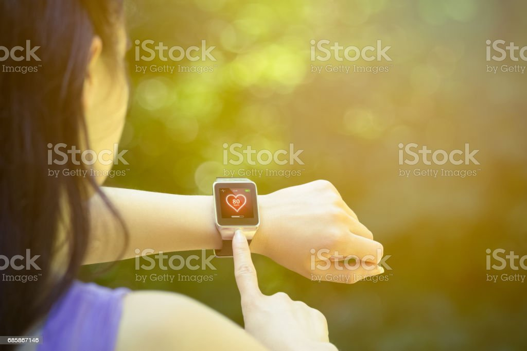 Female runner checking heart rate on smart watch outdoors stock photo