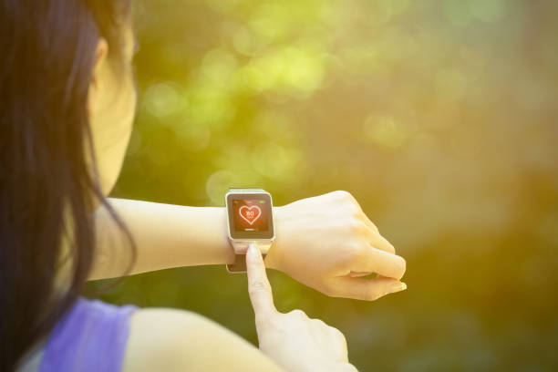 Corredor fêmea que verific a taxa de coração no relógio esperto ao ar livre - foto de acervo