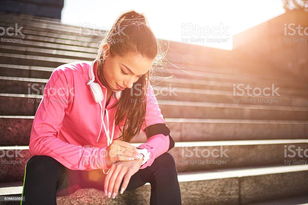 Mujer Corredor revisando información sobre reloj inteligente - foto de stock