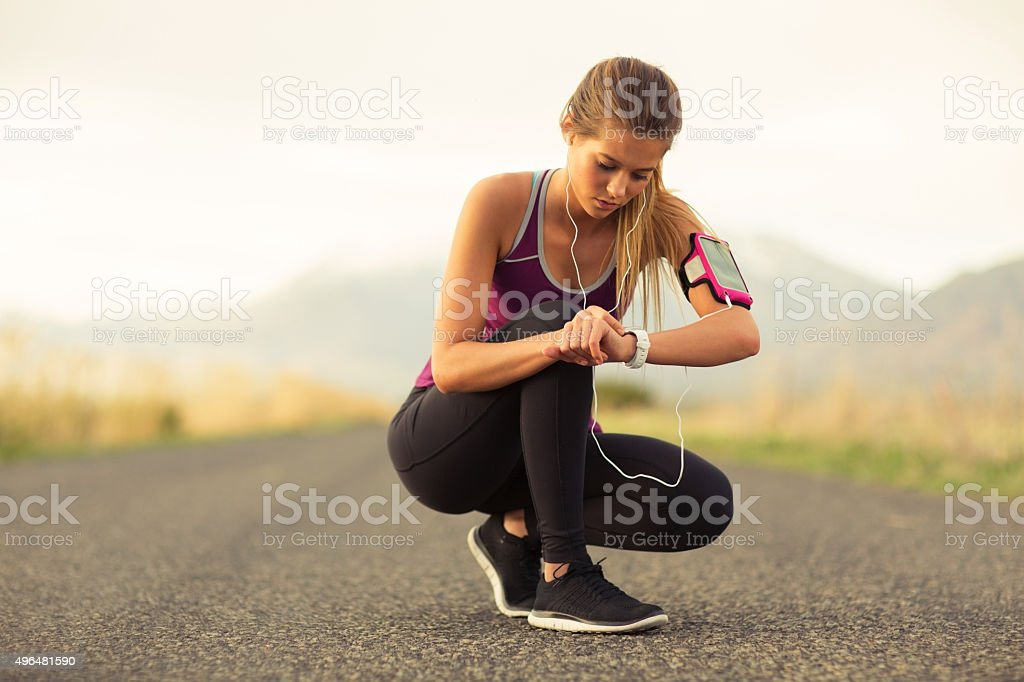 Female Runner Checking Time Along Road in Utah stock photo