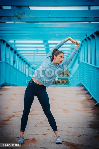 Young woman doing core side bend exercise outdoors before going for a jog