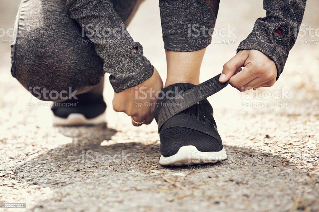 Female runner fastening velcro closure of shoe stock photo