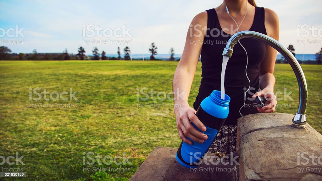 Female runner fills up water bottle outdoors stock photo