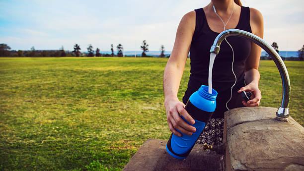Female runner fills up water bottle outdoors - foto de stock
