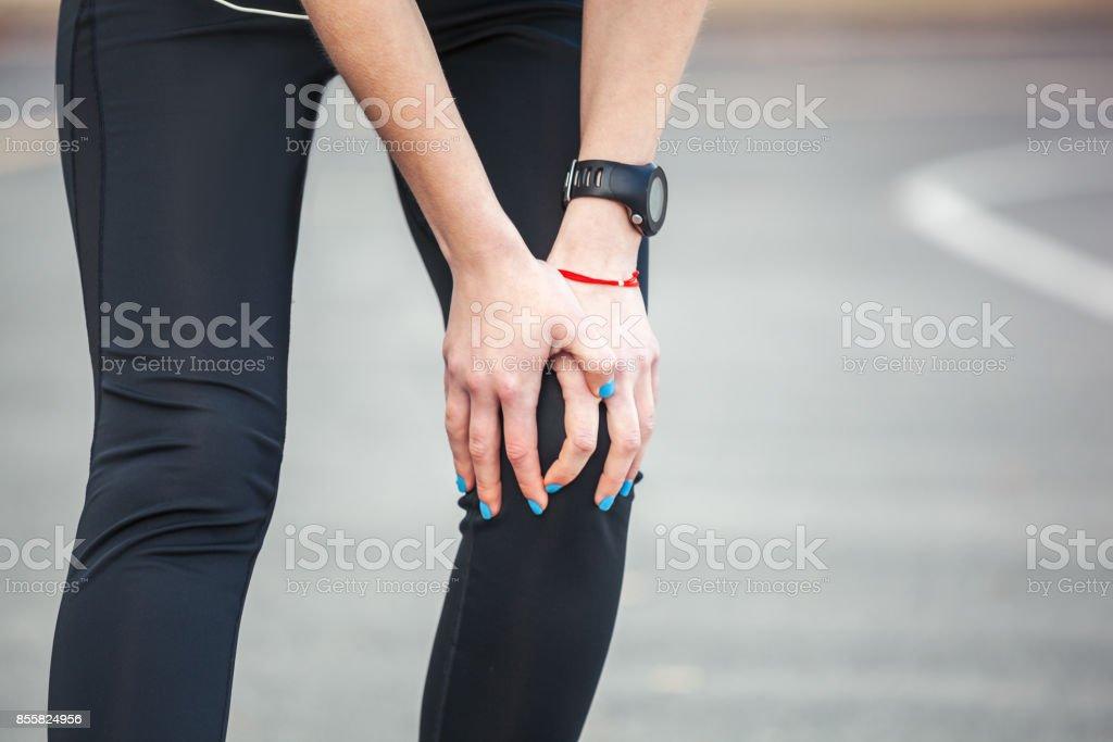 Female runner is holding her injured leg. stock photo