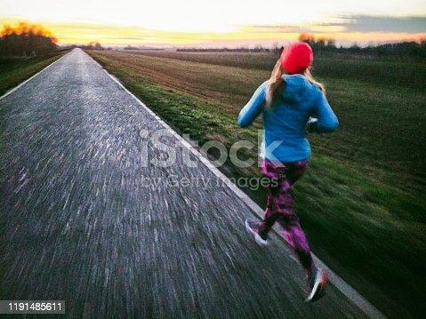 Running on the asphalt road in the middle of nowhere. Rough grain, motion blur, genuine scene. Taken on mobile device.