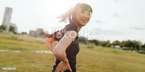 istock Female runner laughing on field in morning 596086200