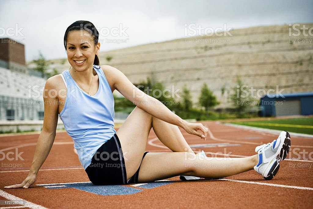 female runner leg stretching on the track royalty-free stock photo
