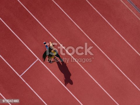 Young female professional athlete listening to music and training by sprinting on running track