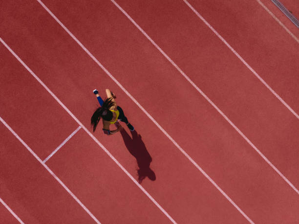Female runner listening to music and running on sports track stock photo