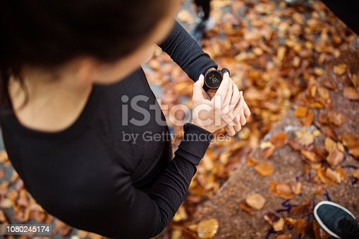 Top view of female runner looking at her smart watch while taking break from sports training outdoors. Woman using heart rate monitor app on her smart watch.