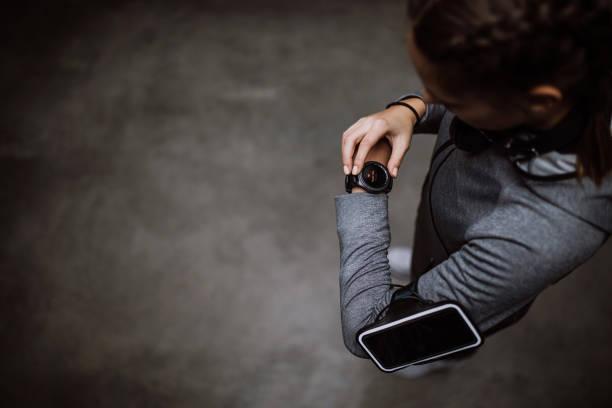 runner femme regardant moniteur de fréquence cardiaque montre intelligente - chrono sport photos et images de collection