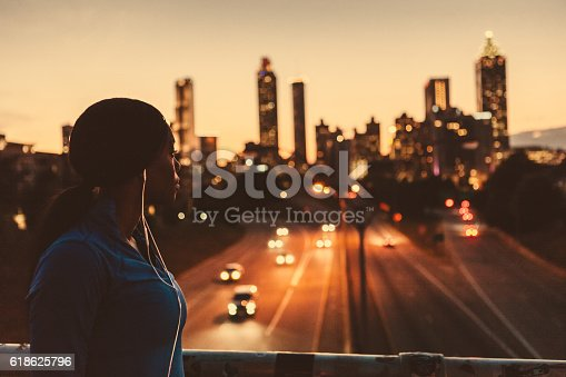 Women jogger wearing earbuds and stopping to take a look a the skyline.