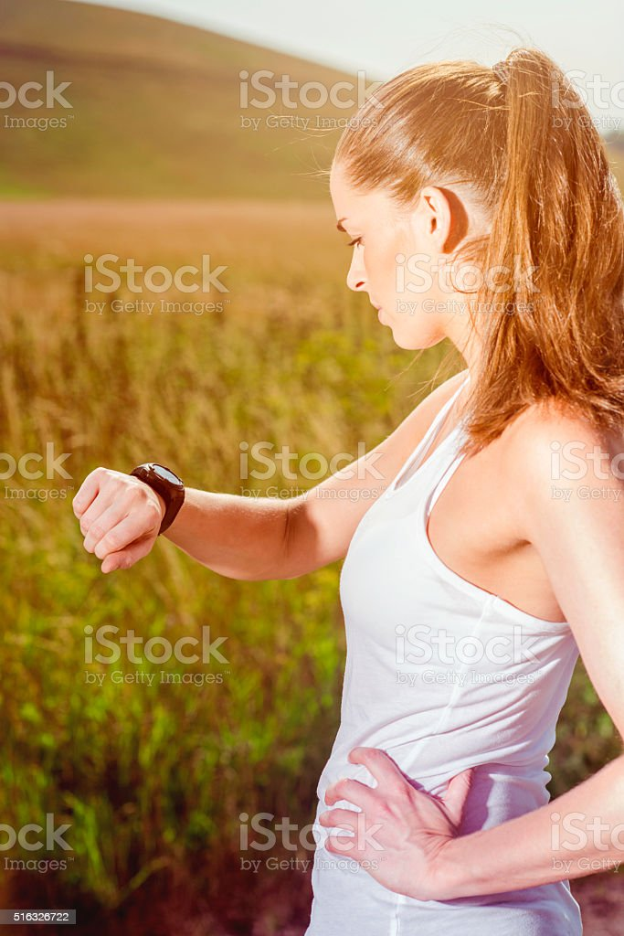 Female runner looks at her smart watch outside stock photo
