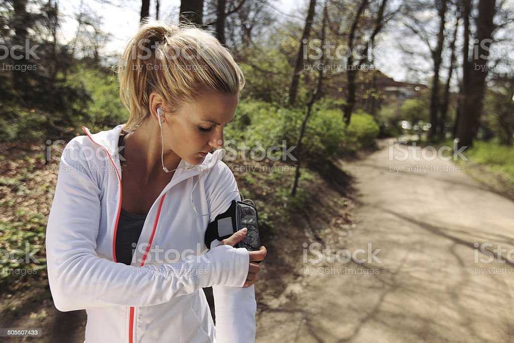 Female runner monitor her progress on smartphone stock photo