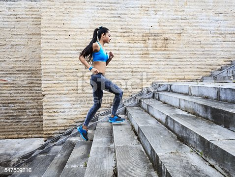 Female athlete running up on stairs, side view, Wears sports clothes in gray and blue and sneackers, with blue smart watch. Stone wall on background.