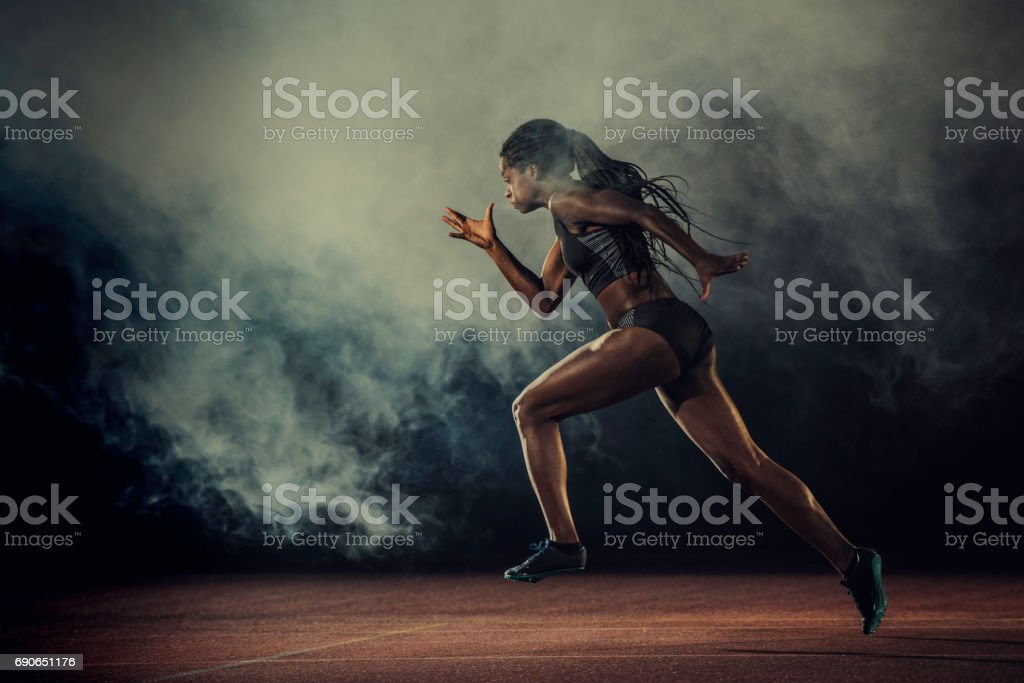 Female runner of African descent in mid-air stock photo