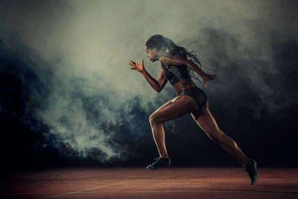 female runner of african descent in mid-air - corsa su pista femminile foto e immagini stock