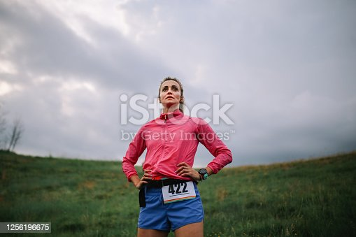A female athlete standing and posing after running a marathon in the nature.