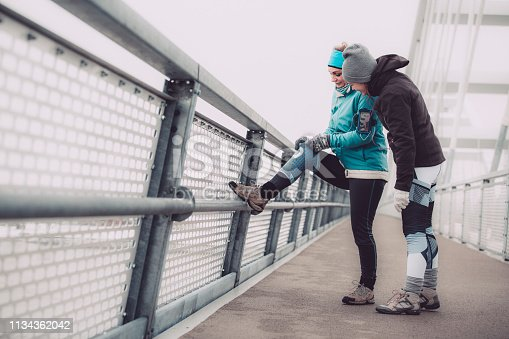 Two Caucasian women are standing on a city bridge and preparing for training on a cold winter day.