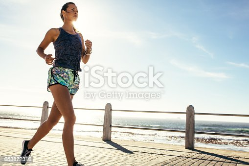 istock Female runner running along the road by the sea 653872316