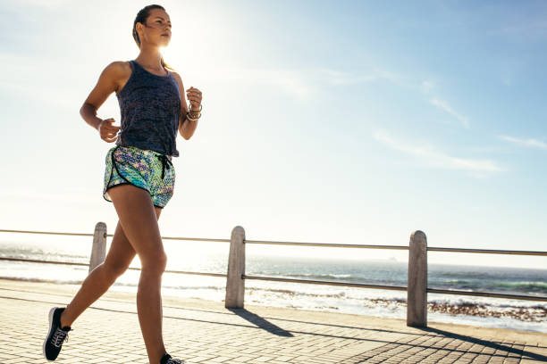 Female runner running along the road by the sea stock photo