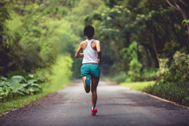Female runner running at summer park trail . Healthy fitness woman jogging outdoors. stock photo