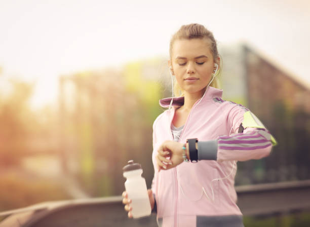 Female runner running at sunset in city park - Healthy fitness woman jogging outdoors - Athlete listening to music during workout at park and adjusting smart watch stock photo