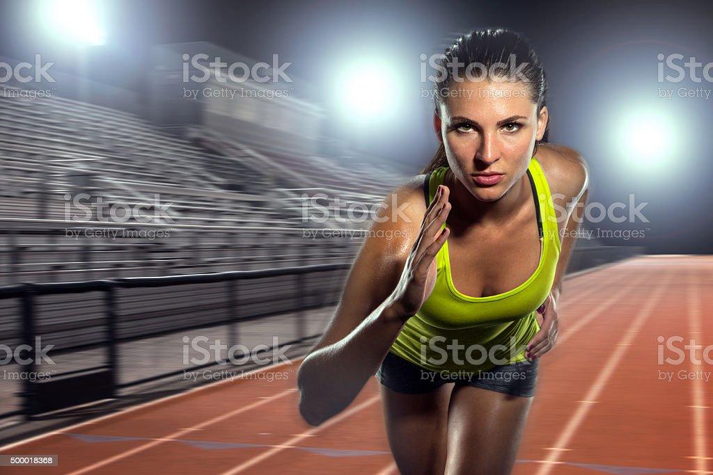 Female runner sprinter exercising training intense track field athlete sports stock photo