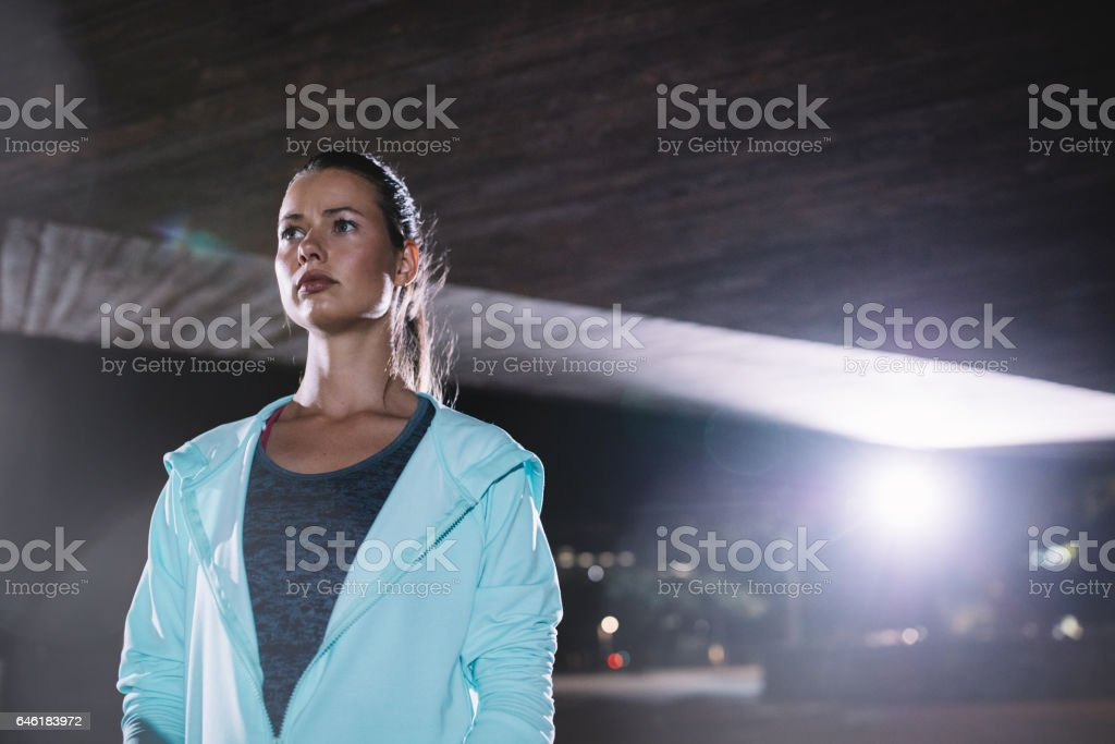 Female runner standing under bridge at night – Foto