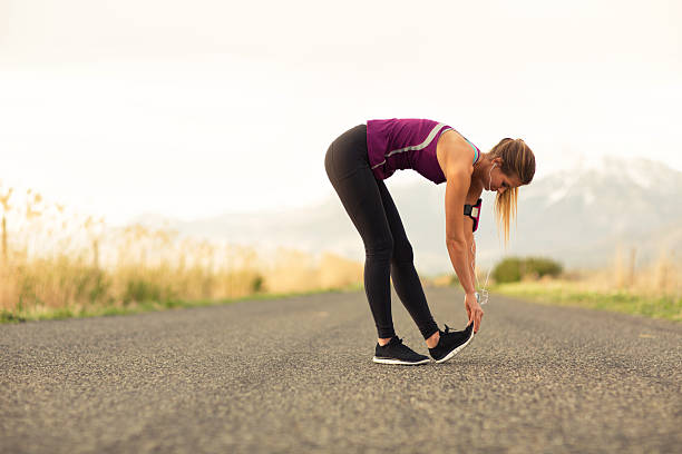Female Runner Stretches Along Road in Utah A fit female stretches her hamstring muscle while standing along a road in Utah. She is geared up with her music ready for her weekend run. hamstring stock pictures, royalty-free photos & images