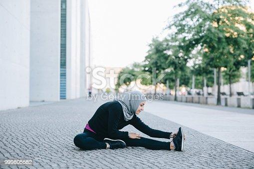 istock Female runner stretching her legs on the street 999805582
