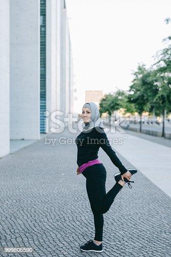 istock Female runner stretching her legs on the street 999805590