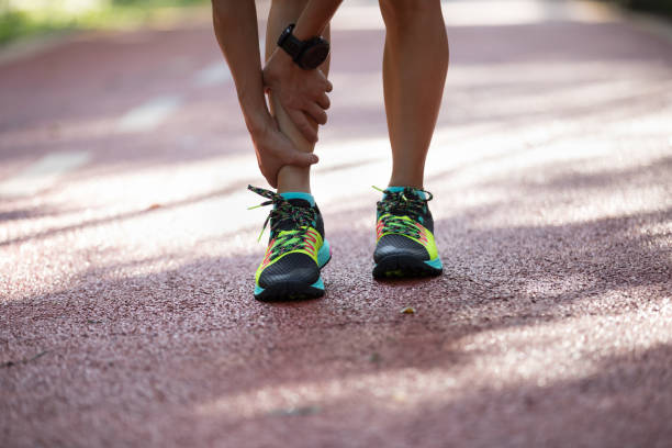 Female runner suffering with pain on sports running injury stock photo
