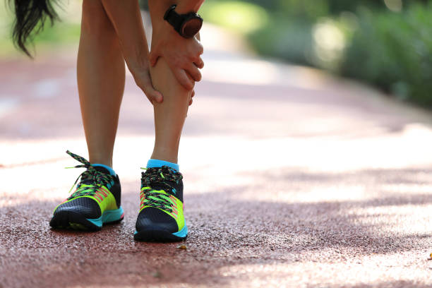 coureur féminin souffrant de douleur sur des dommages de fonctionnement de sports - mi jambe photos et images de collection