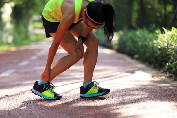 スポーツランニング傷害の痛みに苦しむ女性ランナー - 脛 ストックフォトと画像