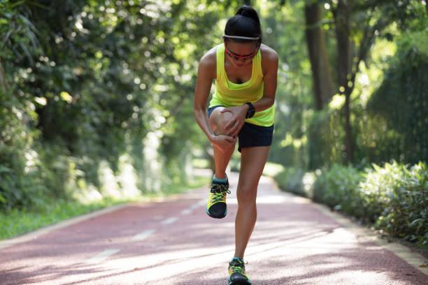 スポーツ走行の膝の怪我の痛みで苦しんでいる女性ランナー - 脛 ストックフォトと画像