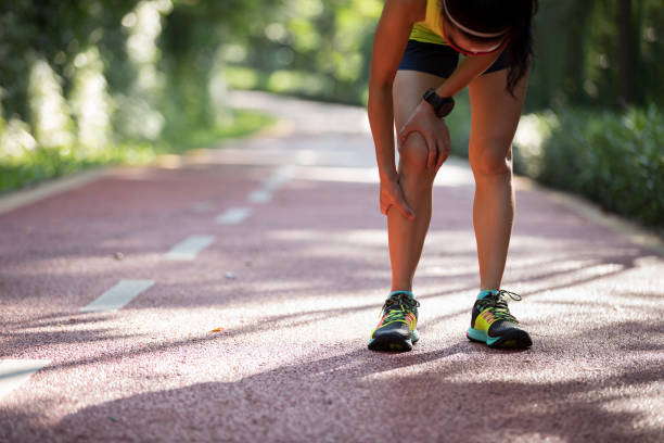 Female runner suffering with pain on sports running knee injury stock photo