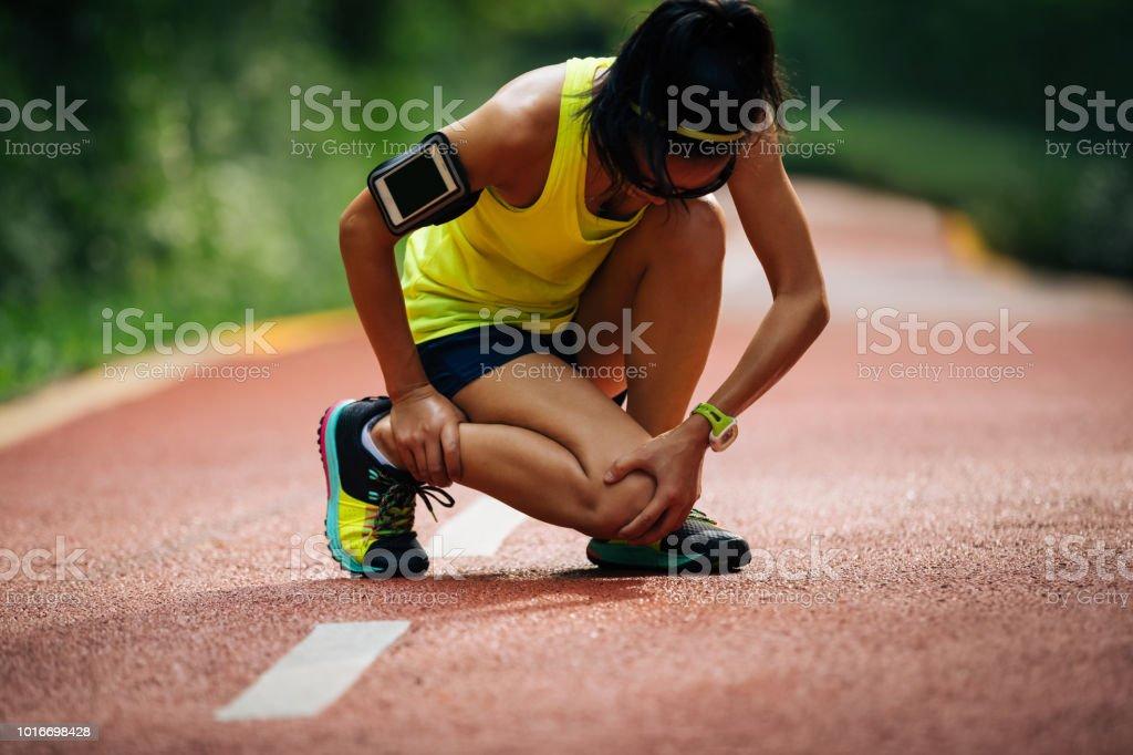 Female runner suffering with pain on sports running knee injury – zdjęcie
