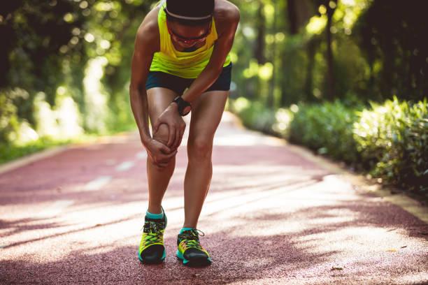 Läuferin leidet mit Sportverletzung beim Laufen – Foto