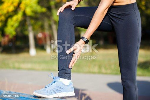 istock Female runner touching cramped calf at jogging 859849206
