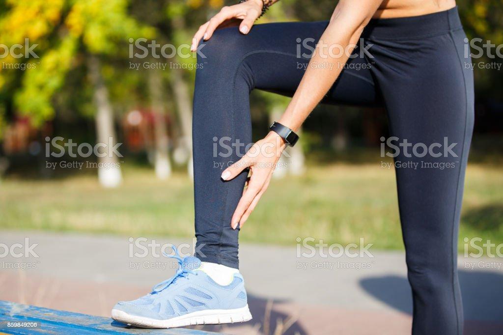 Female runner touching cramped calf at jogging stock photo