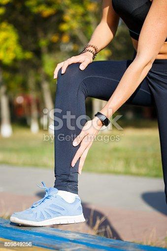 istock Female runner touching cramped calf at jogging 859849256